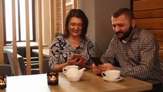 Couple sitting in the restaurant and looking on mobile phone drink caffee