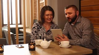 Couple with tablet computer in cafe