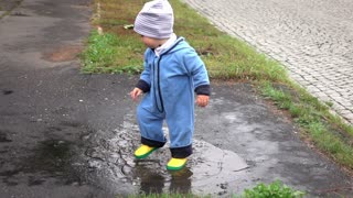 Cute baby boy is playing in puddle, slow motion