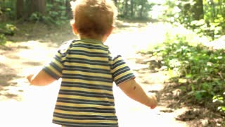 Cute baby is a running at the forest path