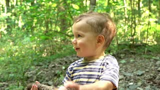 Cute baby is playing with stick at the forest