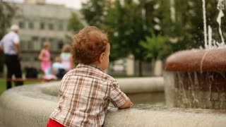 Cute kid is playing near fountain at the city