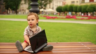 Cute kid is sitting on a bench with laptop