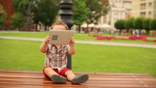 Cute kid is sitting on a bench with tablet