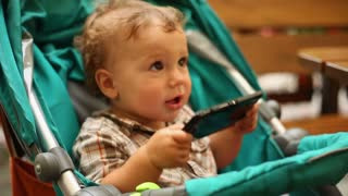 Cute kid with smartphone is dancing in the stroller