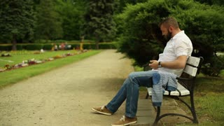 Father plays with little son, sitting on a bench at the park