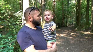 Father with sad son is walking at the forest