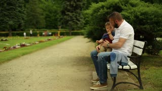 Father with son sitting on a bench at the park