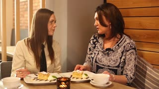 Female friend comforting sad woman in the cafe