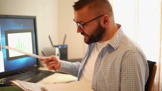 Handsome businessman working from home office doing paper work