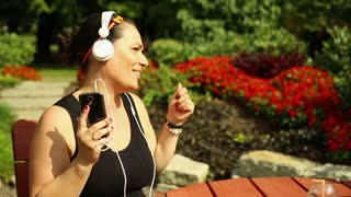 Happy woman is listening to music in the park