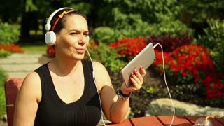 Happy woman is listening to music on a tablet in the park