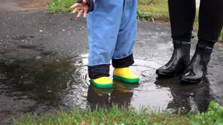 Legs mother and baby in puddle, slow motion
