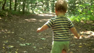 Little boy is a running at the forest path