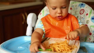 Little boy is eating spaghetti with hands