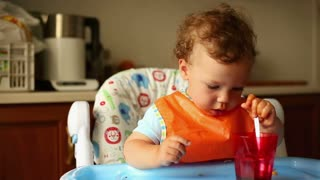 Lovely boy with glass and spoon in the kitchen