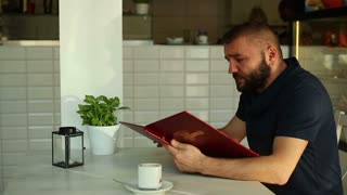 Male man reading menu in cafe