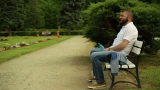 Man drinks water, sitting on a bench at the park