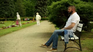 Man in park waits, sitting on a bench