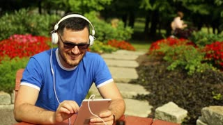 Man is listening music on tablet in the park
