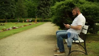 Man listening music at the smartphone, sitting on a bench at the park