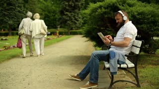 Man listening music at the tablet, sitting on a bench at the park