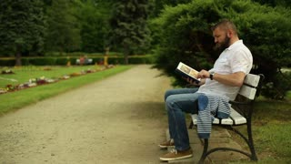 Man reads book, sitting on a bench at the park