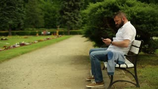 Man sends sms and talking for cell phone, sitting on a bench at the park