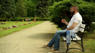 Man sneeze, sitting on a bench at the park