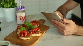 Man using tablet in restaurant, closeup