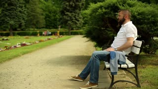 Man with headache sits on a bench at the park