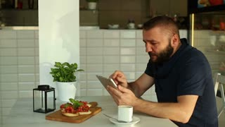 Man with tablet eating sandwich in cafe