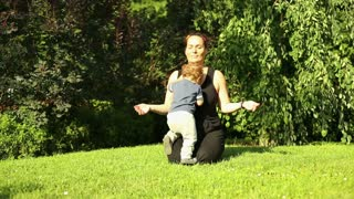 Mother is meditating at the park, little son is hinder