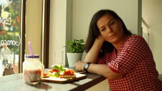 Pensive woman sitting alone in restaurant