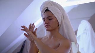 Pretty woman applying cream on her hands in the bathroom