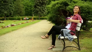 Pretty young woman drinking coffee and relaxing in the park