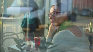 Sad, depressed woman sitting in cafe
