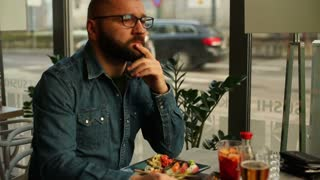 Sad, depressed young man looking to camera in restaurant