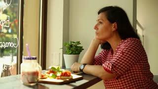 Sad, pensive woman drinking orange juice in cafe