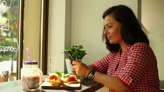 Smile woman typing sms on her smartphone in restaurant