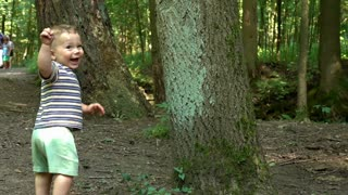 Sweet baby playing peek-a-boo near tree at the forest