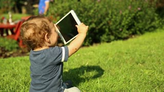 Sweet kid is sitting on the grass in the park and playing with a tablet