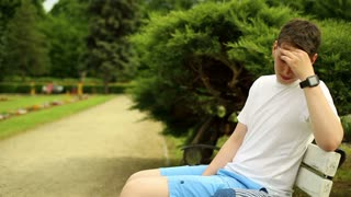Teenager collapsed, sitting on a bench at the park