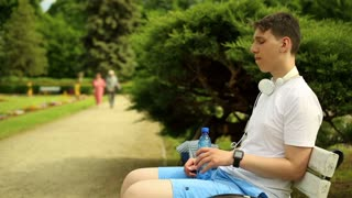 Teenager drinks water, sitting on a bench at the park