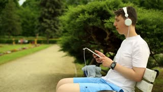 Teenager listening music in tablet at the park