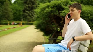 Teenager talking for cell phone, sitting on a bench at the park