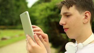 Teenager with tablet at the park