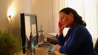 Tired businesswoman having headache during work with documents at home