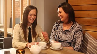 Two female friends chatting in restaurant