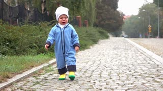 Unhappy baby boy is walking on road, slow motion